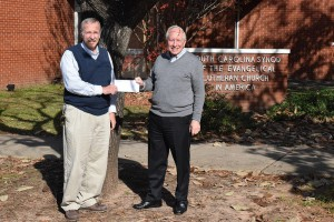 Pastor Bob Beaver, right, accepts a check from Pastor David Sprang at the SC Synod office.