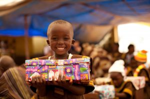A Liberian boy is elated with his package – perhaps the first gift he's ever received.